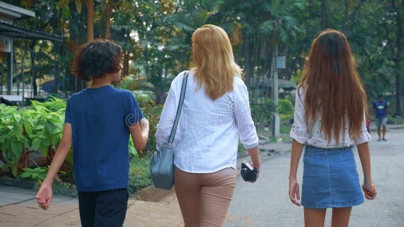 Kvinnan med barn-, son- och dottertonåringar med en kamera går till och med gatorna av en stor modern stad royaltyfri bild