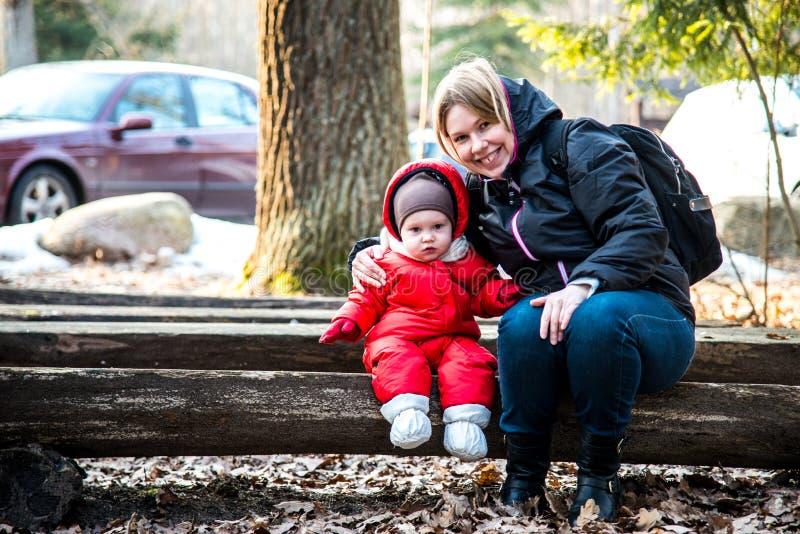 Kvinnan med barnet parkerar in bänken, familjstående royaltyfria foton