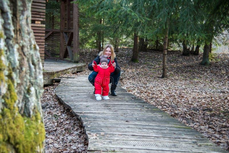 Kvinnan med barnet parkerar in slingan av träbanan royaltyfria foton