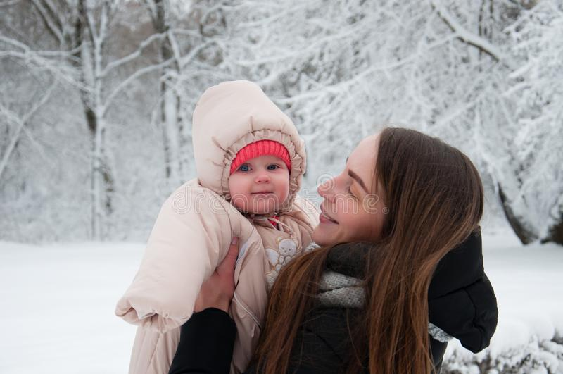 Kvinnan med behandla som ett barn flickan i vinter parkerar arkivbilder