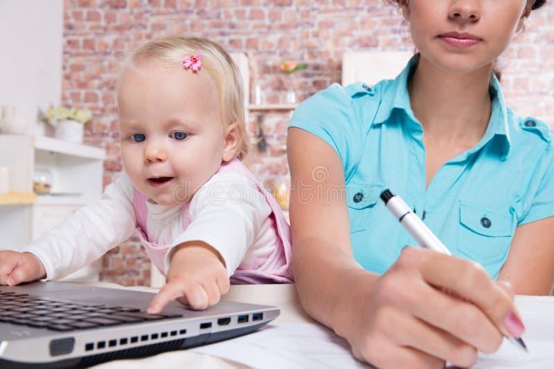 Kvinnan med behandla som ett barn i köket som arbetar med bärbara datorn arkivfoto
