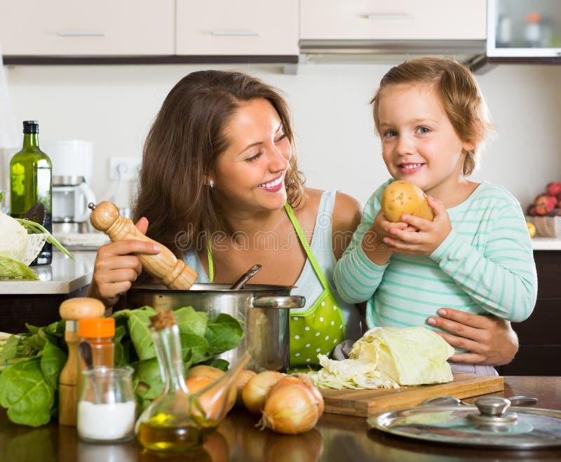 Kvinnan med behandla som ett barn matlagning på kök arkivbild