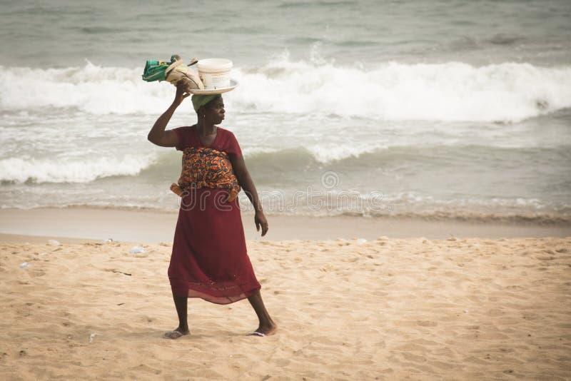 Kvinnan med behandla som ett barn på en strand i uddekusten, Ghana fotografering för bildbyråer