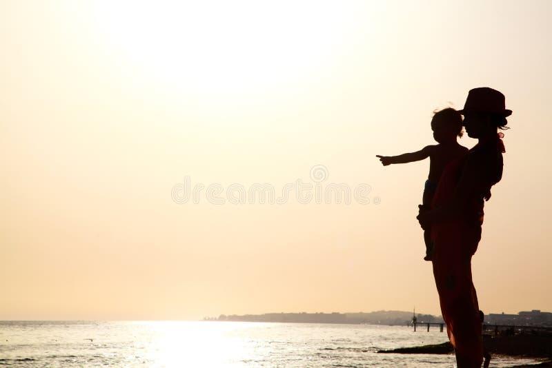 Kvinnan med behandla som ett barn på solnedgången arkivfoto