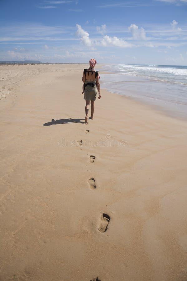 Kvinnan med behandla som ett barn ryggsäcken på stranden royaltyfria foton