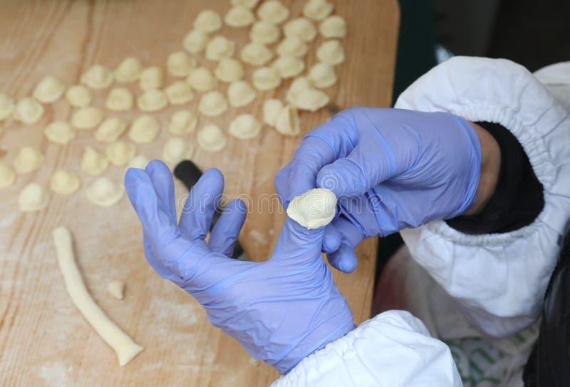 kvinnan med blåa handskar gör den italienska pastan som kallas Orecchiett arkivfoto
