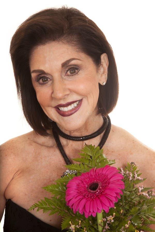 Kvinnan med blommor stänger leende fotografering för bildbyråer