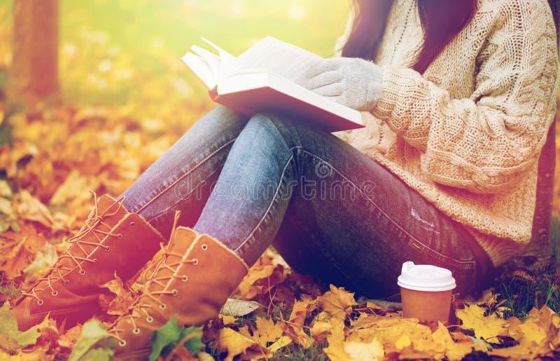 Kvinnan med boken som dricker kaffe i höst, parkerar royaltyfri foto