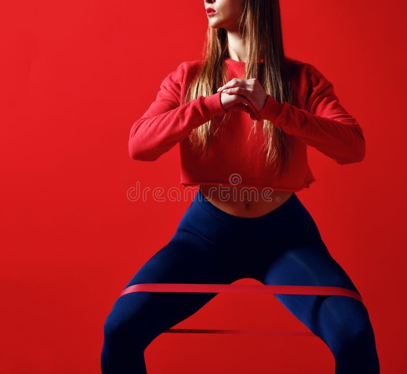 Kvinnan med bra fysik som gör sträckning, utarbetar med elastiska musikband arkivfoto