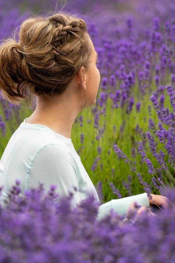 Kvinnan med brunetthår sitter och ser bort, medan posera i ett fält av lavendelblommor i Sequim Washington royaltyfria foton