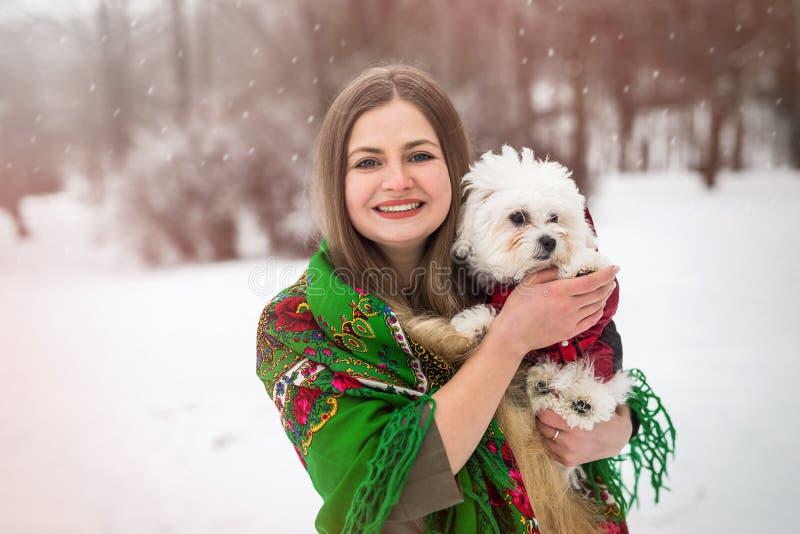 kvinnan med den lilla vita hunden i vinter parkerar royaltyfri foto
