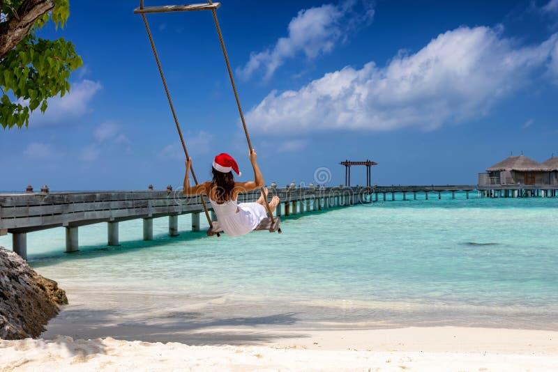 Kvinnan med den röda Santa Claus hatten sitter på en gunga på en tropisk strand royaltyfri bild