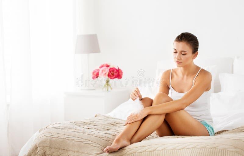 Kvinnan med den rörande fjädern gör bar ben på säng royaltyfria bilder