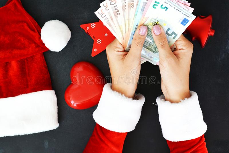 Kvinnan med den Santa's dräkten med kontanta eurosedlar som föreslår hög ferie, uppta som omkostnad arkivfoto