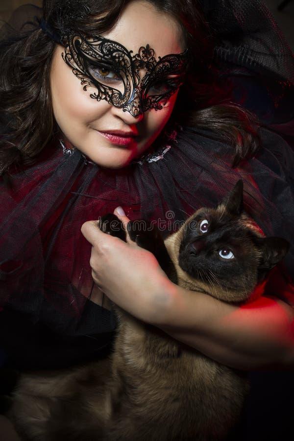 Kvinnan med den siamese katten, att ha på sig som är venetian, maskerar royaltyfri bild