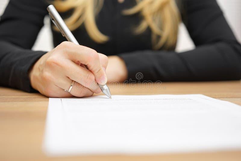 Kvinnan med den svarta skjortan undertecknar det lagliga dokumentet royaltyfri fotografi