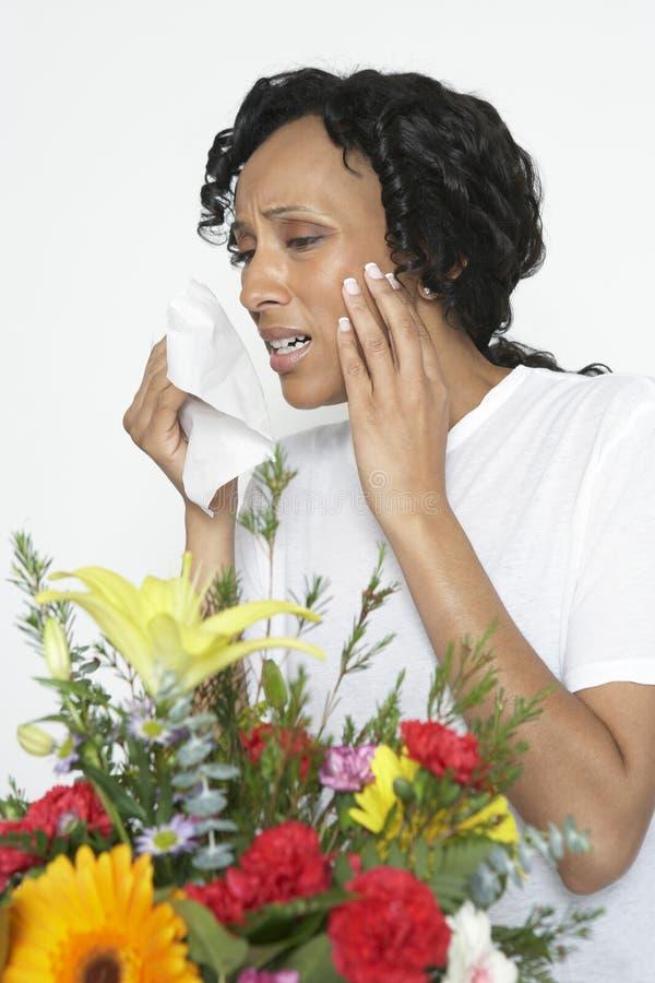 Kvinnan med det hållande silkespappret för allergin nära blommar fotografering för bildbyråer