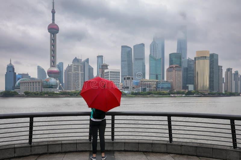 Kvinnan med det röda paraplyet tycker om sikten till horisonten av Shanghai, Kina fotografering för bildbyråer