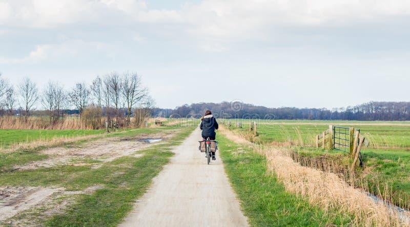 Kvinnan med det svarta omslaget cyklar på en grusväg i en plan agricultu royaltyfria foton