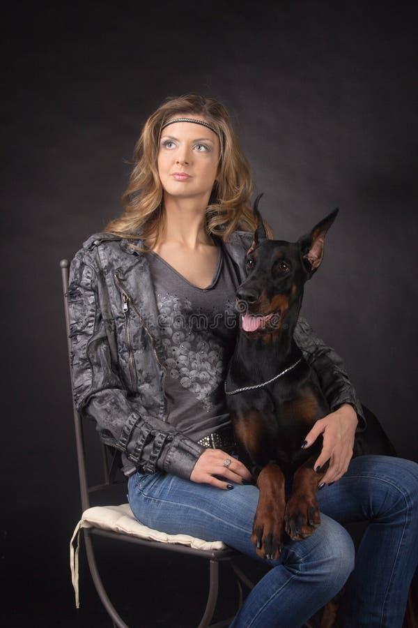 Kvinnan med dobermann förföljer arkivbild