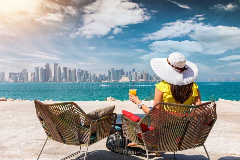 Kvinnan med en fruktsaft i hennes hand tycker om sikten till horisonten av Doha, Qatar royaltyfri fotografi