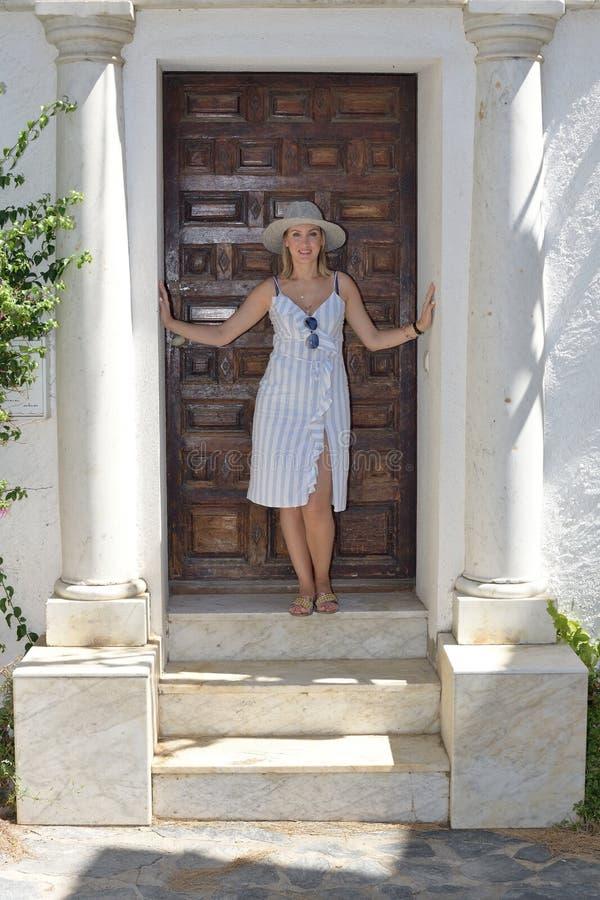 Kvinnan med en hatt som framme ser kameran av en lantlig brun trädörr med vita joniska kolonner, marmorerar moment och vit arkivfoto