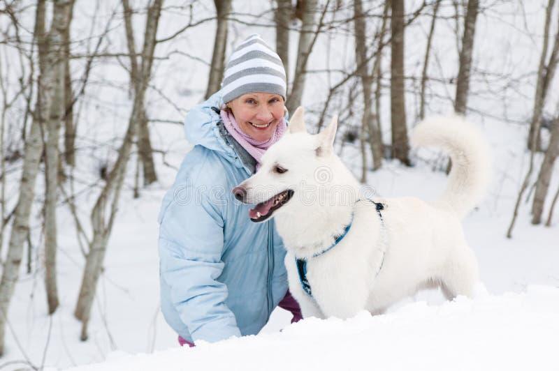 Kvinnan med en hund i vinter går arkivfoto