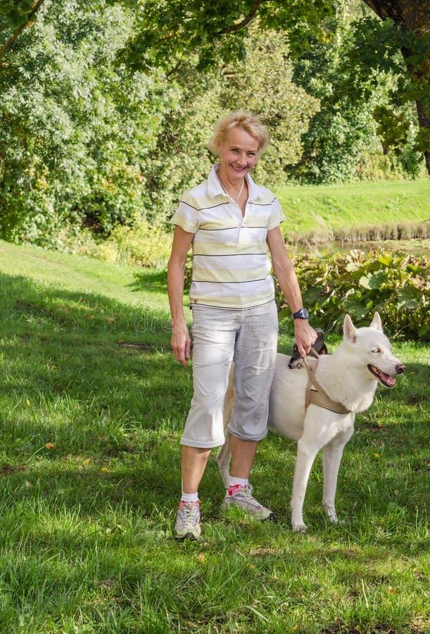 Kvinnan med en hund på en gå parkerar in royaltyfri foto
