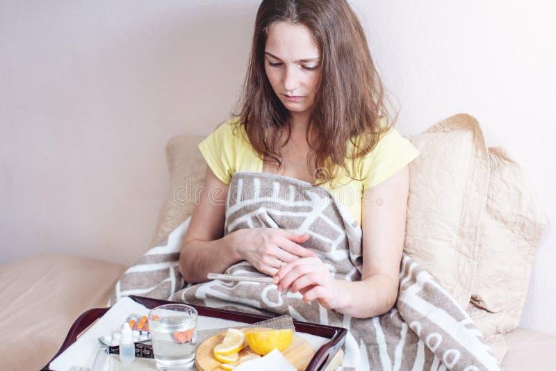 Kvinnan med en huvudvärk och en influensa i säng behandlas med minnestavlor och vitaminer Säsongsbetonade förkylningar i vinter royaltyfria bilder