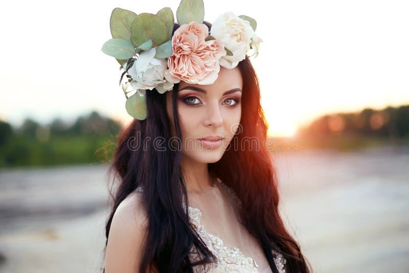 Kvinnan med en krans av blommor på hennes huvud och en sommar klär wa royaltyfria bilder