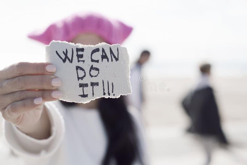 Kvinnan med en rosa hatt och texten kan vi göra den arkivbild