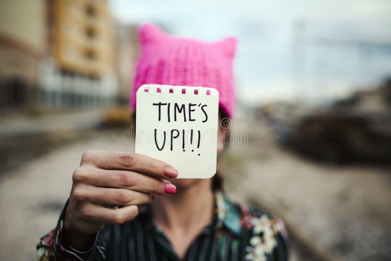 Kvinnan med en rosa hatt och texttiden är upp royaltyfri bild