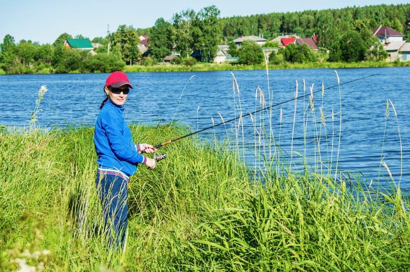 Kvinnan med en roteringsstång fångar en fisk i sjön royaltyfria bilder