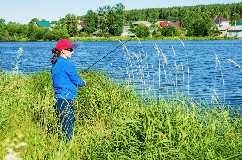 Kvinnan med en roteringsstång fångar en fisk i sjön arkivfoto