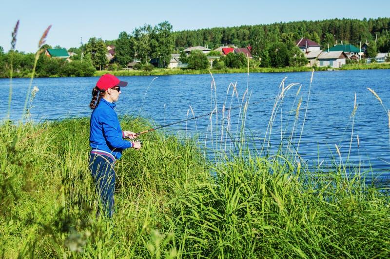 Kvinnan med en roteringsstång fångar en fisk i sjön fotografering för bildbyråer