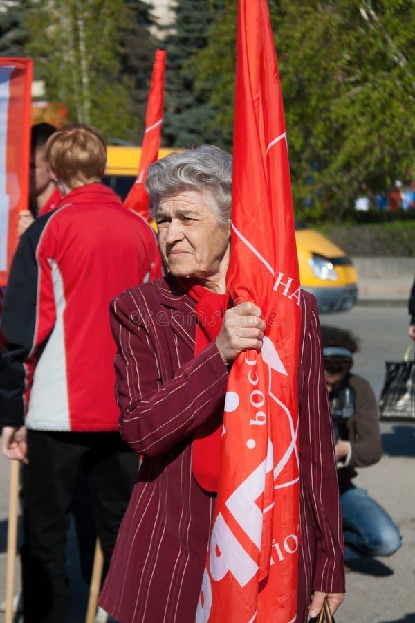Kvinnan med flaggatagande särar i demonstrationen för den Maj dagen i Volgograd royaltyfria foton