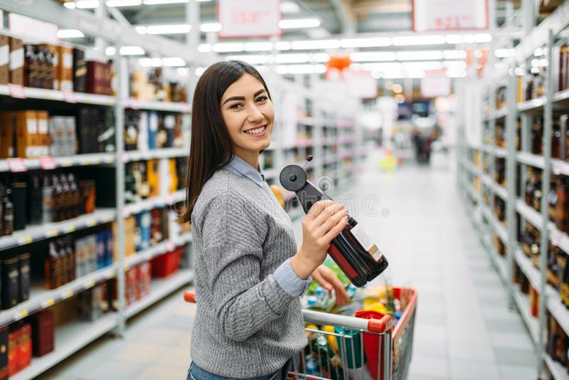 Kvinnan med flaskan av alkoholdrycken shoppar in fotografering för bildbyråer