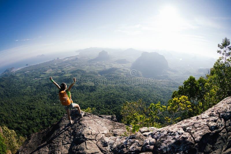 Kvinnan med fotvandrare tycker om sikten på bergöverkant royaltyfri bild