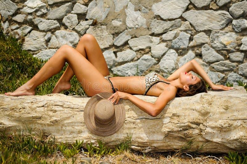 Kvinnan med härligt förkroppsligar ha på sig bikini- och sunhatten fotografering för bildbyråer