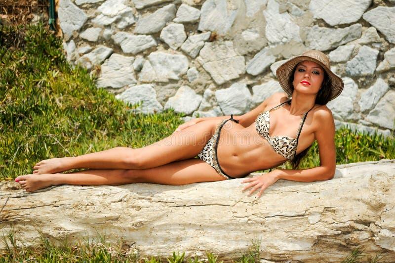 Kvinnan med härligt förkroppsligar ha på sig bikini- och sunhatten royaltyfria foton