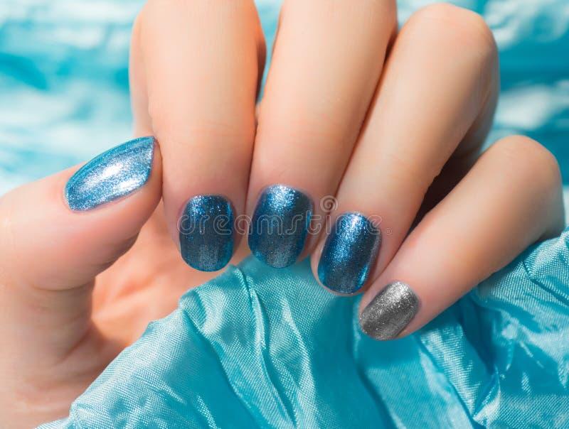 Kvinnan med härligt spikar blåa fingernaglar som korsar behagfullt hennes händer för att visa dem till tittaren på, försilvrar ba royaltyfria foton