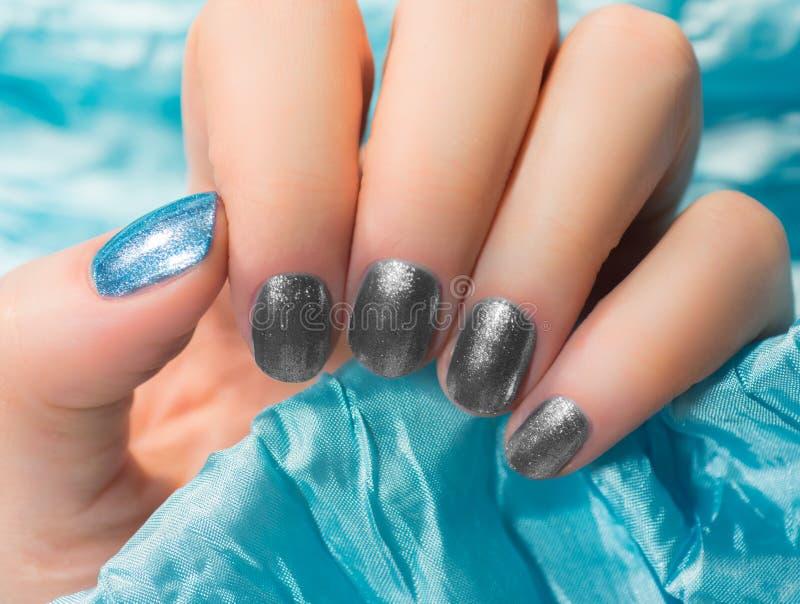 Kvinnan med härligt spikar blåa fingernaglar som korsar behagfullt hennes händer för att visa dem till tittaren på, försilvrar ba fotografering för bildbyråer