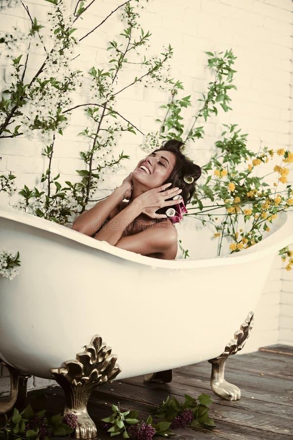 Kvinnan med hårrullar på hår sitter i badet, kroppomsorg royaltyfri bild