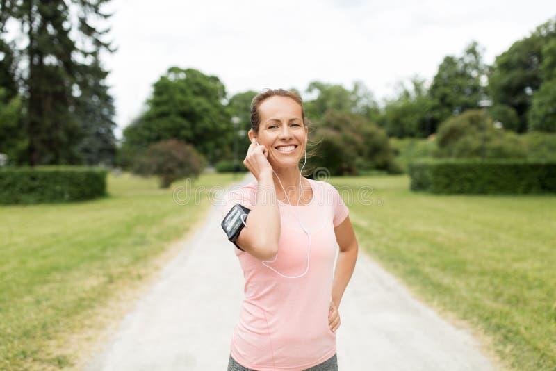 Kvinnan med hörlurar och armbindeln på parkerar arkivbilder