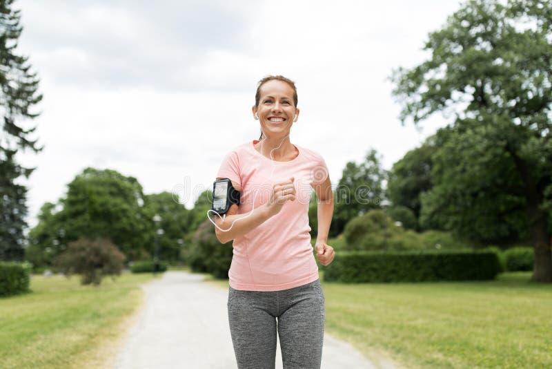 Kvinnan med hörlurar och armbindeln som joggar på, parkerar royaltyfria foton