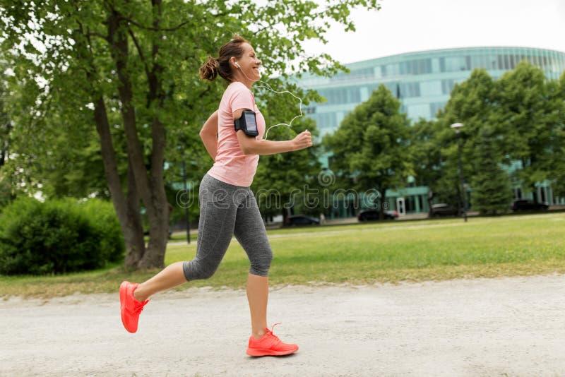 Kvinnan med hörlurar tillfogar armbindeln som joggar på, parkerar arkivfoton