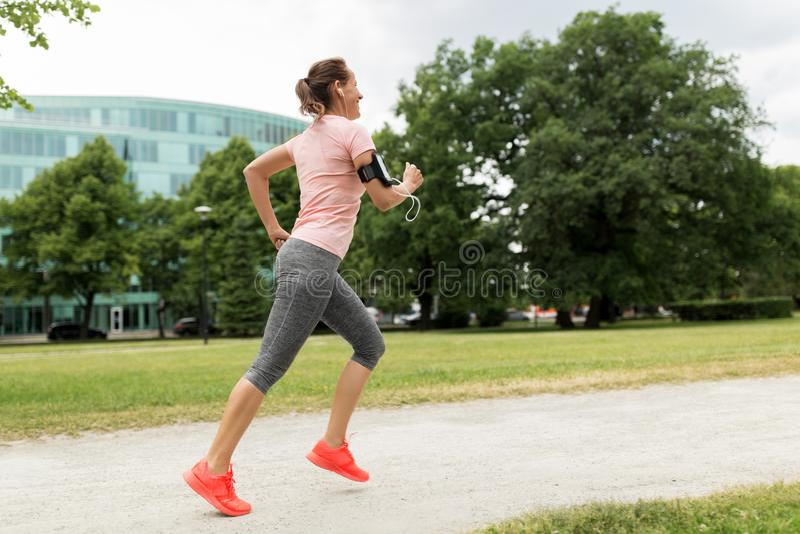 Kvinnan med hörlurar tillfogar armbindeln som joggar på, parkerar arkivbild