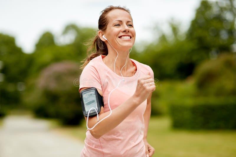 Kvinnan med hörlurar tillfogar armbindeln som joggar på, parkerar arkivfoto