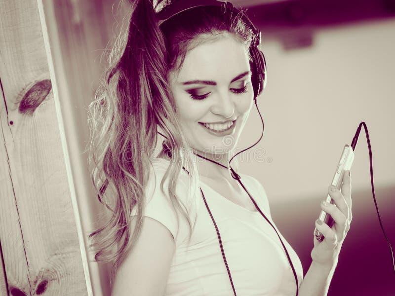 Kvinnan med hörlurar väljer musik på smartphonen arkivfoton