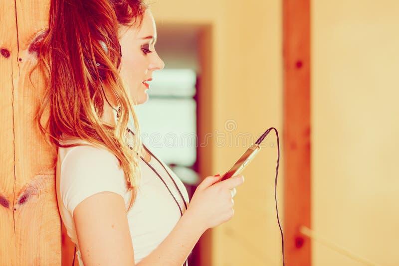 Kvinnan med hörlurar väljer musik på smartphonen royaltyfri foto
